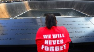 A woman takes a moment to mourn lost relatives at the memorial site of the now destroyed World Trade Center, New York, the US, September 11, 2013.