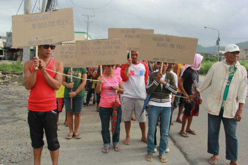 Residents hold improvised placards declaring their opposition to the 'No Build Zone' policy. Photo from Tudla