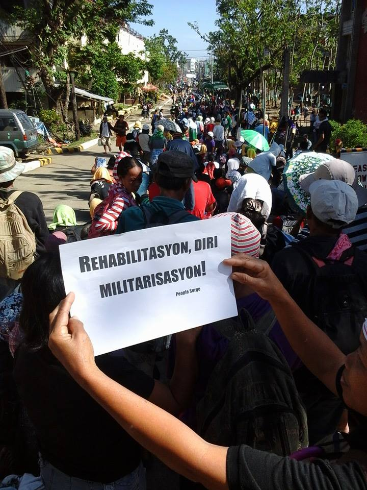 A participant of the rally calls for immediate rehabilitation of typhoon-affected villages instead of militarization. Photo from Tudla