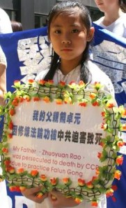 A young girl holds a memorial wreath for her father during an event in New York
