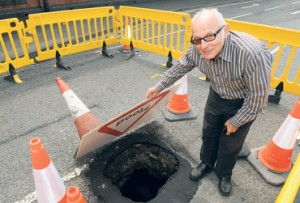 Mr Malcolm Peet examines the hole on Queen's Road. 200514DD3-7