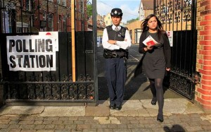 A police officer stands outside a polling station in Tower Hamlets as a lady leaves after casting her vote during the European elections