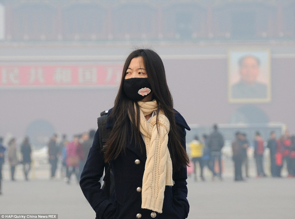 Citizens: This woman wore a mask as she stood in Beijing's iconic Tian'anmen Square. Citizens were told to stay indoors earlier this week and builders had to abandon their posts
