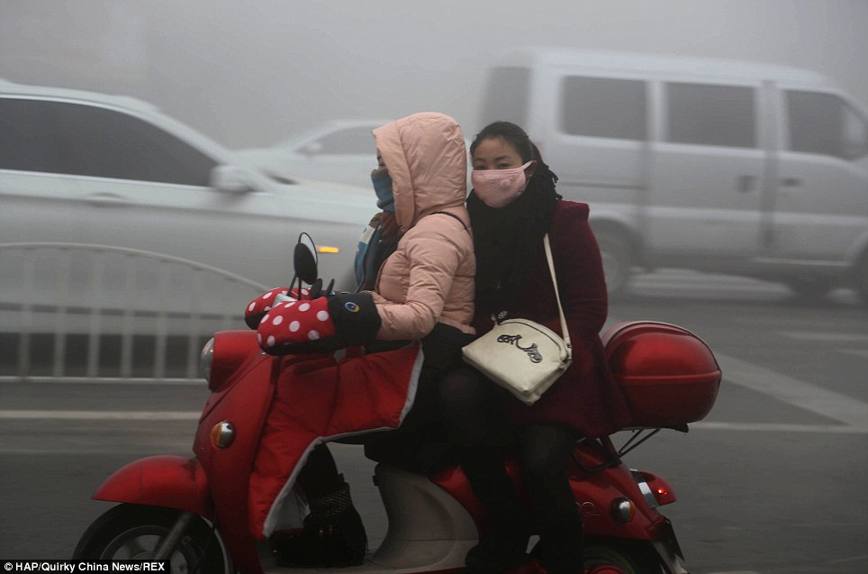 Covered up: Women wear improvised cloth masks to protect themselves from the band of smog in Xuchang, Henan Province, where pollution has also reached harmful levels