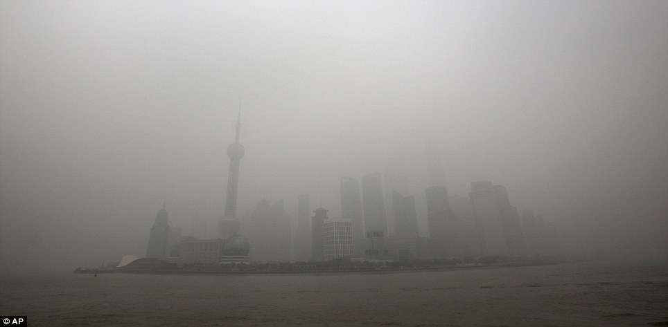 Pea-souper: Shanghai was barely visible through the dirty air in this photo, taken on Monday. The pollution is attributed to coal burning, car exhaust, factories and weather