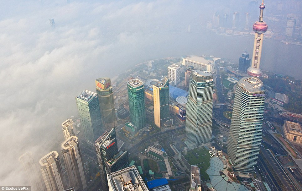 Hazardous: In Shanghai, the iconic skyline including the 1,535ft Oriental Pearl Tower (right) appeared marooned by a thick swirl of smog, which has left citizens at risk of cancer