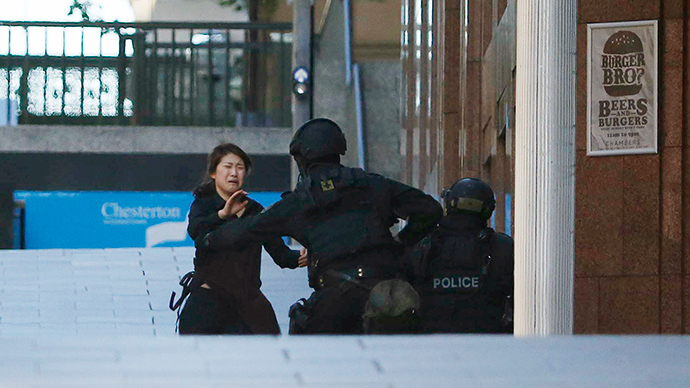A hostage runs towards a police officer outside Lindt cafe, where other hostages are being held, in Martin Place in central Sydney December 15, 2014 (Reuters / Jason Reed)