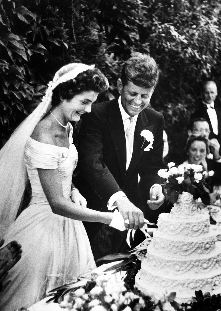 Wedding of Jacqueline Bouvier and John F. Kennedy. Reception at Hammersmith Farm, Newport, Rhode Island, 12 September 1953. Bride and Groom cut wedding cake.