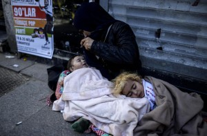 A Syrian refugee woman begs with her children on the street  in the Beyoglu district of Istanbul on April 17, 2015. AFP PHOTO / BULENT KILIC
