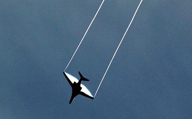 a US-led coaliton plane flies above the Syrian border town of Kobani (Ayn al-Arab) on October 23, 2014.