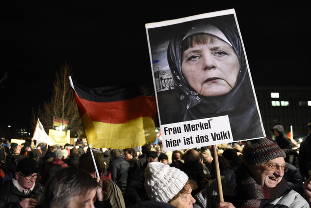A protestor holds a poster with a picture of German Chancellor Angela Merkel reading 'Mrs Merkel, her is the people' during a rally of the group Patriotic Europeans against the Islamization of the West, or PEGIDA, in Dresden, Germany, Monday, Jan. 12, 2015. (AP Photo/Jens Meyer)