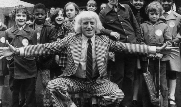 Predator Savile poses with children taking part in his Jim ll Fix It show in 1974