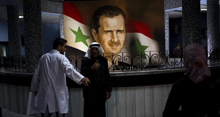 People walk through the Damascus General Hospital past a portrait of the President Bashar Assad in Damascus, Syria, Sunday, May 4, 2014