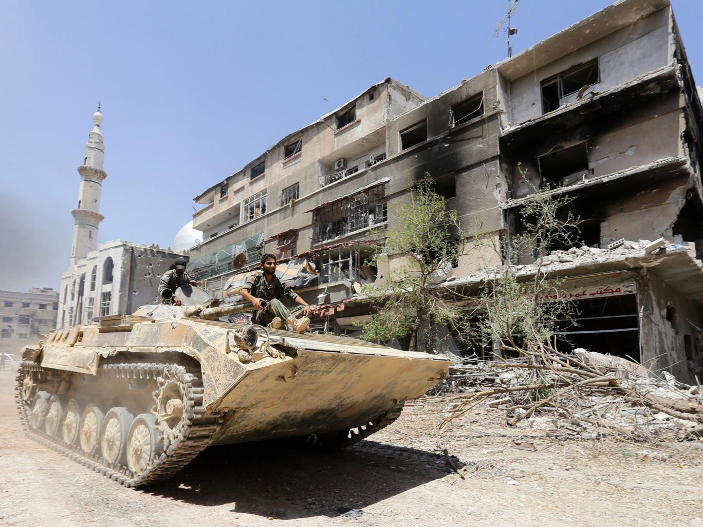 Syrian government troops sit atop a tank as they drive past a damaged building in Mleiha on the outskirts of the capital Damascus on August 15, 2014