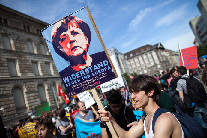 A protester holds a banner featuring German chancellor Angela Merkel reading 'resistance against her Europe' during a Blockupy movement protest on May 17, 2014 in Berlin. The demonstration is directed against the government's refugee policy. AFP PHOTO / DPA/ MAJA HITIJ /GERMANY OUT