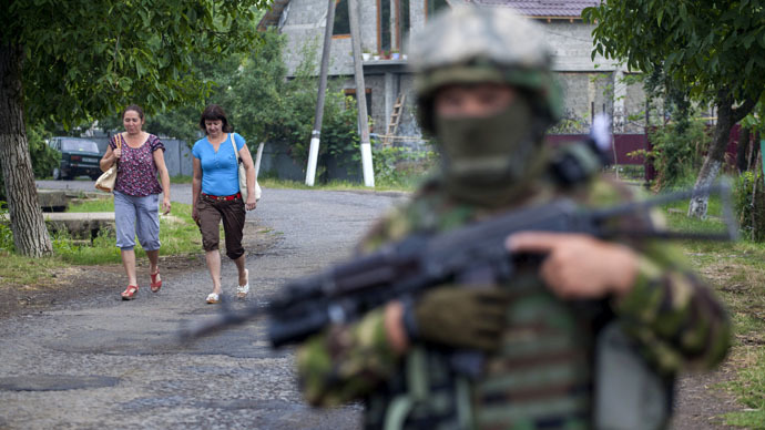 Women walk towards a Ukrainian government serviceman searching for members of Right Sector in the village of Bobovyshche near Mukacheve, Ukraine, July 13, 2015. (Reuters)