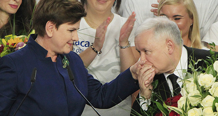 Conservative Law and Justice leader Jaroslaw Kaczynski kisses hand Justice candidate for the Prime Minister Beata Szydlo, left, at the party's headquarters in Warsaw, Poland, on Sunday, Oct.25, 2015