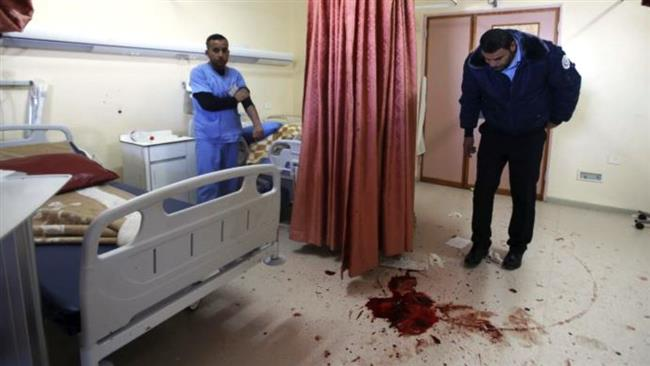 A medic looks at blood stain of a Palestinian man who was killed by Israeli undercover forces during a raid at Al-Ahly hospital in the West Bank city of al-Khalil (Hebron) on November 12, 2015. (Reuters)
