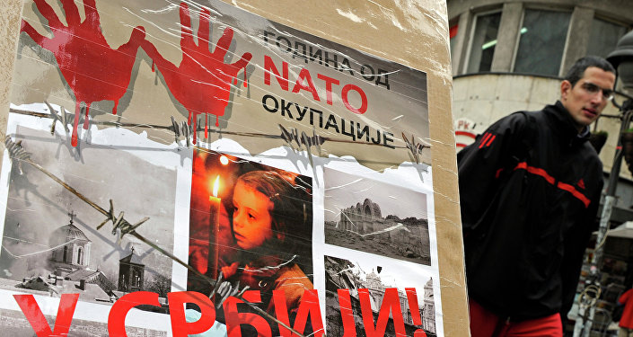 """A man walks past a poster with the reading """"Ten years of NATO occupation of Serbia"""", and displaying images from 1999 NATO air campaign against Serbia and Montenegro, in Belgrade on March 23, 2009."""