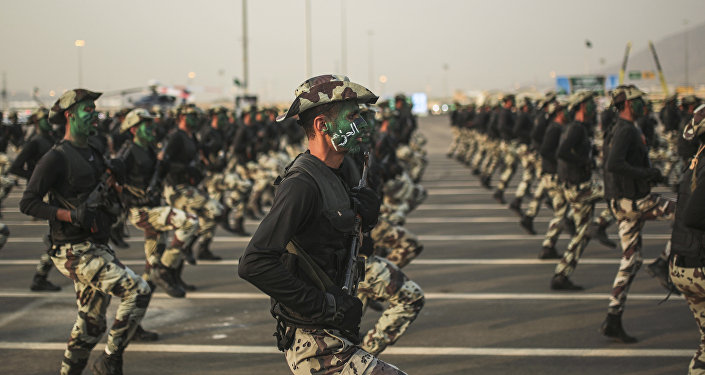 In this Thursday, Sept. 17, 2015 file photo, Saudi security forces, whose faces display the word Decisive take part in a military parade.