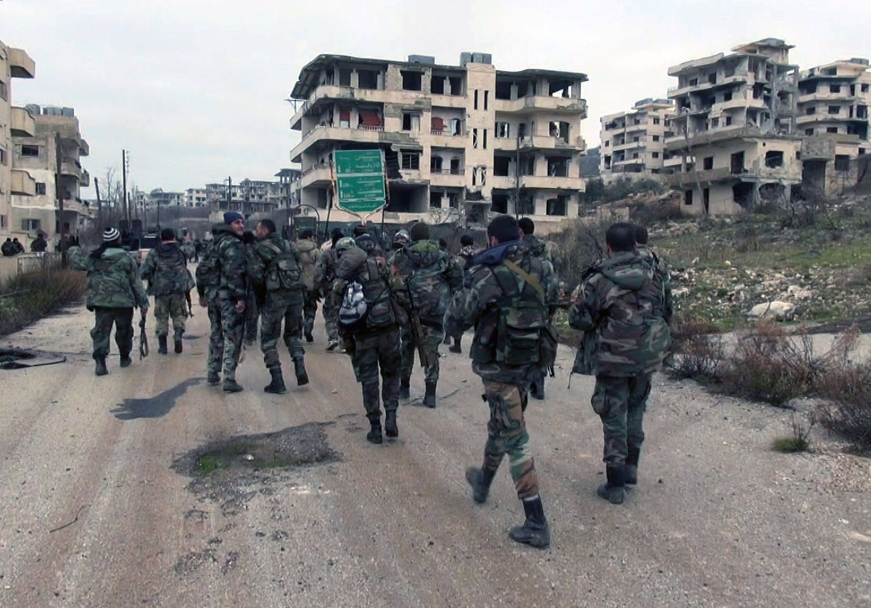 Syrian government troops walk inside the key town of Salma in Latakia province, Syria