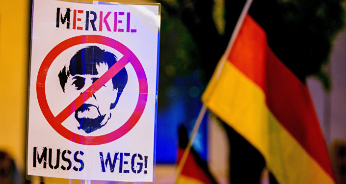 A participant of a rally of the Pegida movement (Patriotische Europaeer gegen die Islamisierung des Abendlandes, which translates to Patriotic Europeans Against the Islamisation of the Occident) holds a sign depicting German chancellor Angela Merkel and reading Merkel must go (Merkel muss weg) in Munich, southern Germany, on November 9, 2015