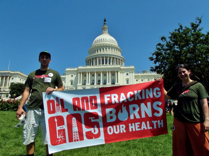 """At the US Capitol in Washington, DC, a pair of activists hold a banner that reads """"Oil and Gas: Fracking Burns Our Health."""" (Flickr / Bill Baker)"""