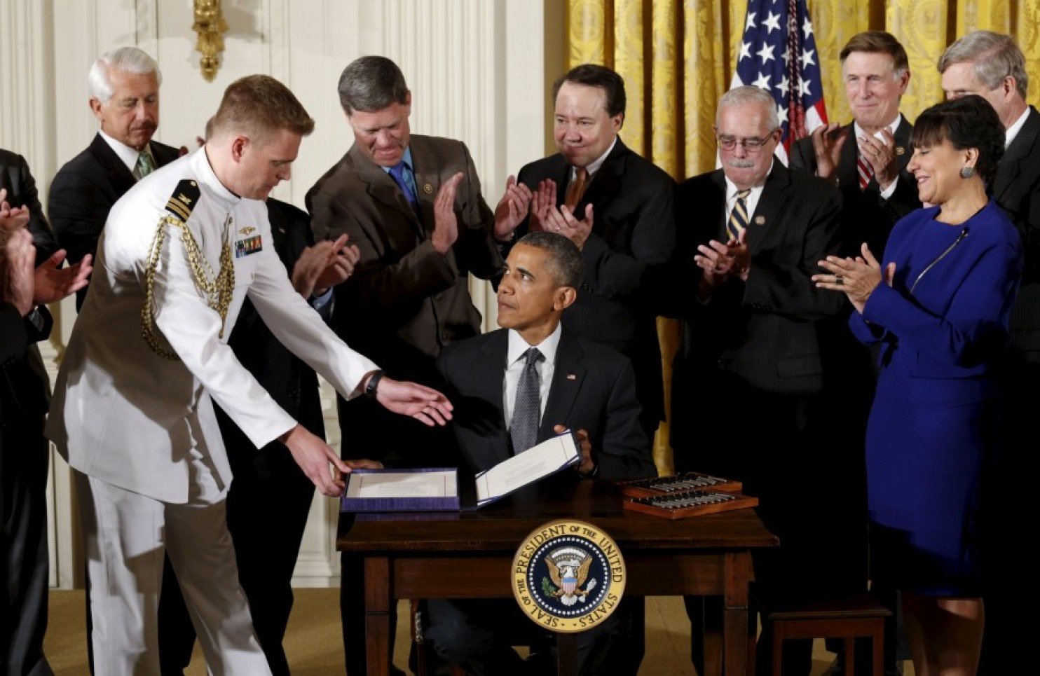 Surrounded by Cabinet officials and members of Congress, President Barack Obama signs H.R. 2146, which sandwiched in other measures, provided a 'fast track; to implementing the TPP. (AP Photo/Carolyn Kaster)
