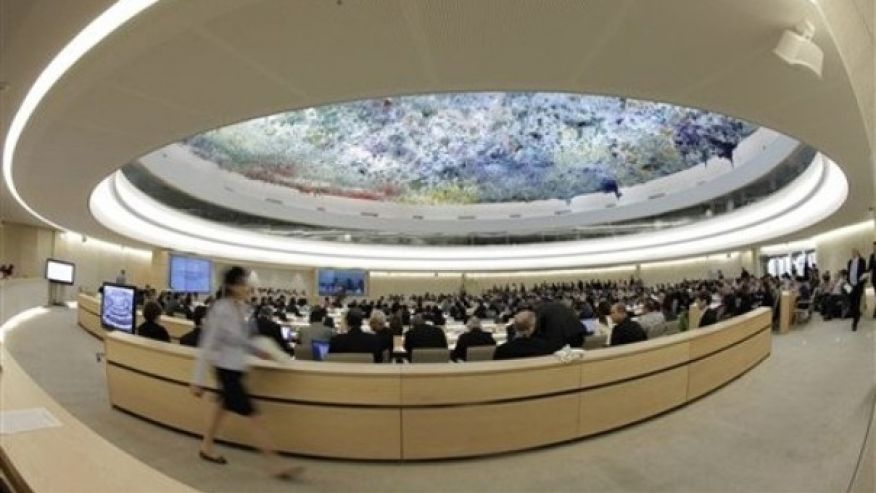 FILE -- A woman walks past the Human Rights Council at the European headquarters of the United Nations in Geneva, Switzerland.