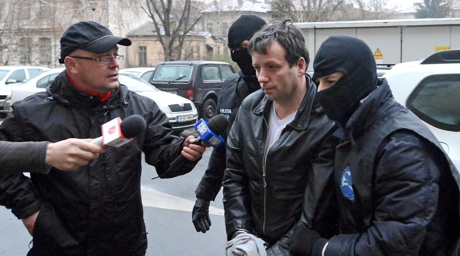 Marcel Lazar Lehel, aka Guccifer, is escorted by masked policemen in Bucharest after his arrest in 2014. © Silviu Matei