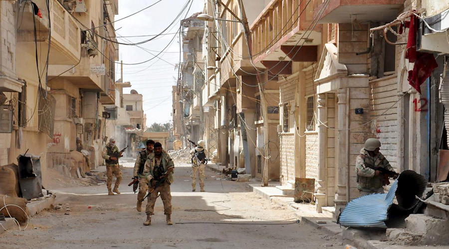 Forces loyal to Syria's President Bashar al-Assad walk with their weapons in Palmyra city after they recaptured it, in Homs Governorate in this handout picture provided by SANA on March 27, 2016. © SANA
