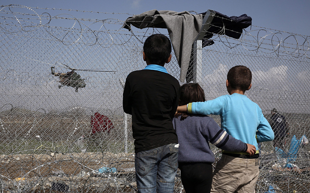 Children watch a helicopter fly over the refugee camp in Idomeni, as migrants and refugees wait to be allowed to cross the border with The Former Yugoslav Republic Of Macedonia (FYROM) in Idomeni, Greece