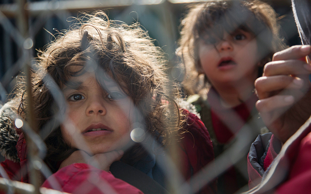 Migrant children await by the fence on the Greek side of the border to enter Macedonia near the southern Macedonian town of Gevgelija