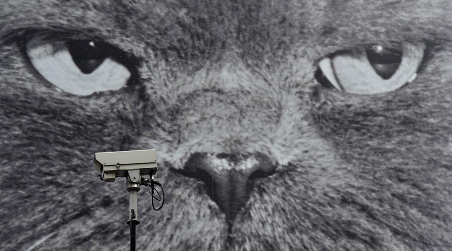 A CCTV camera is seen in front of a large poster opposite a London Underground Station in central London © Toby Melville