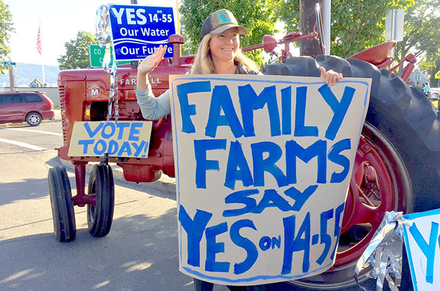 Farmer Moria Reynolds holds a sign in support of 14-55 on primary election day.
