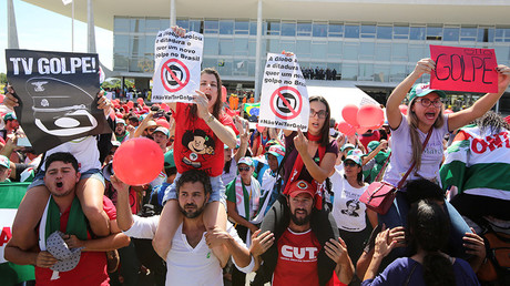 Supporters of suspended Brazilian President Dilma Rousseff show signs reading
