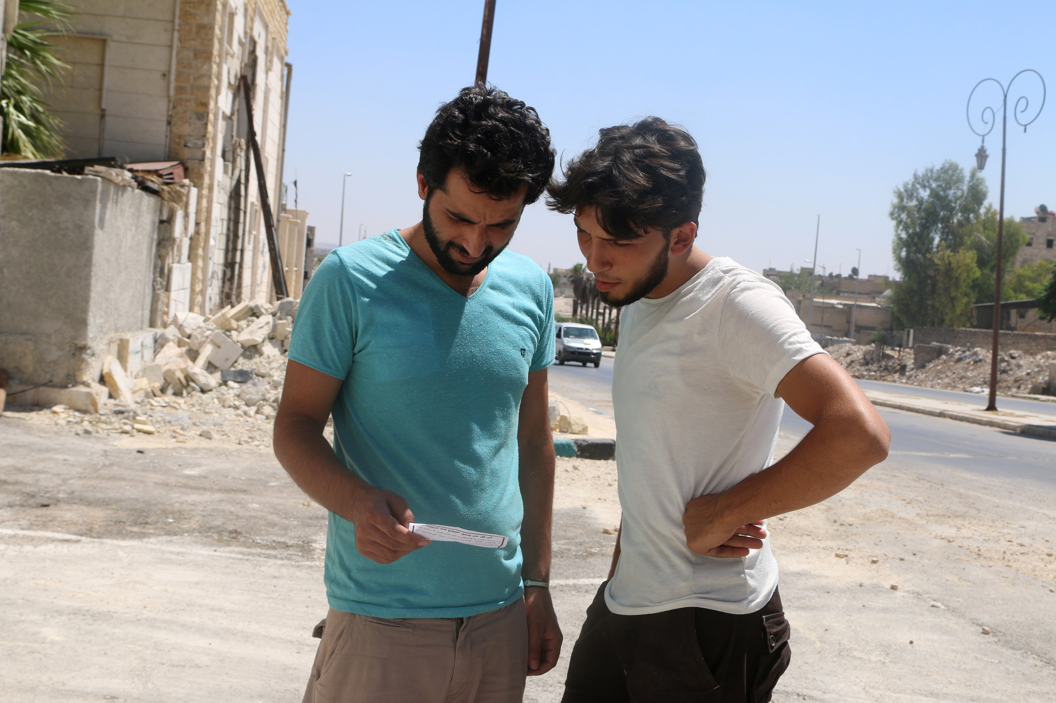 Men read one of the leaflets dropped by the Syrian army over opposition-held Aleppo districts asking residents to cooperate with the military and calling on fighters to surrender, Syria July 28, 2016