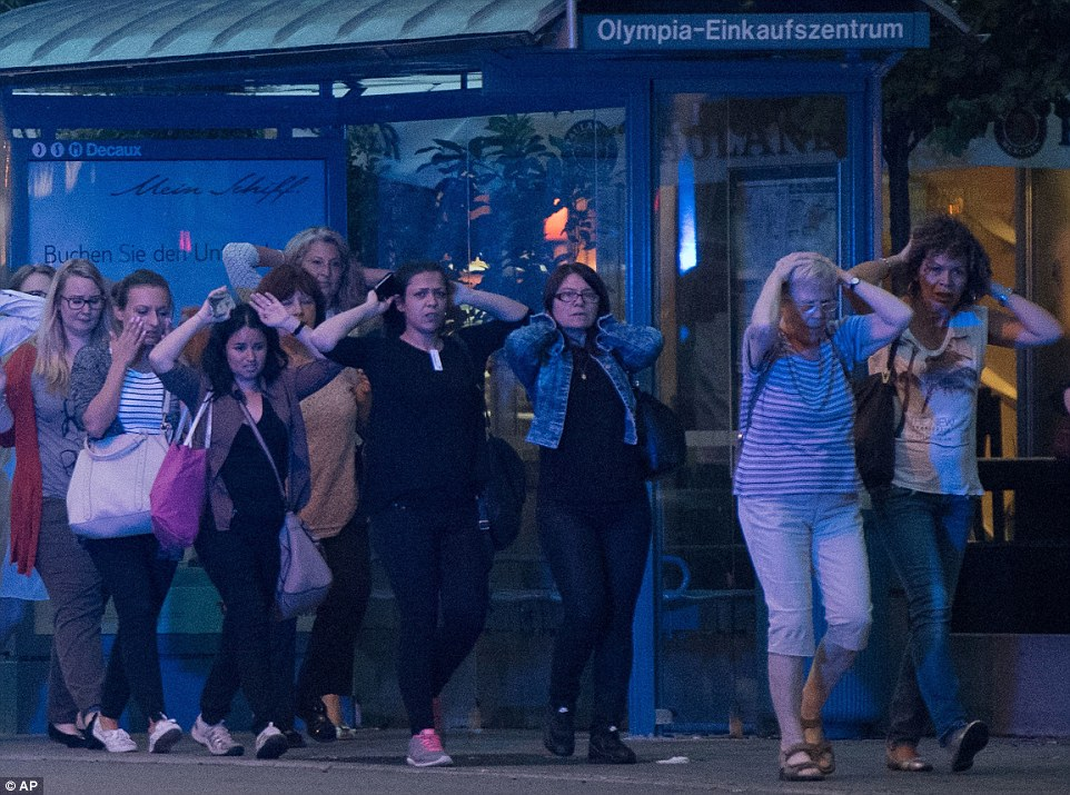 People leave the Olympia mall in Munich, southern Germany, Friday, July 22, 2016 after several people have been killed in a shooting