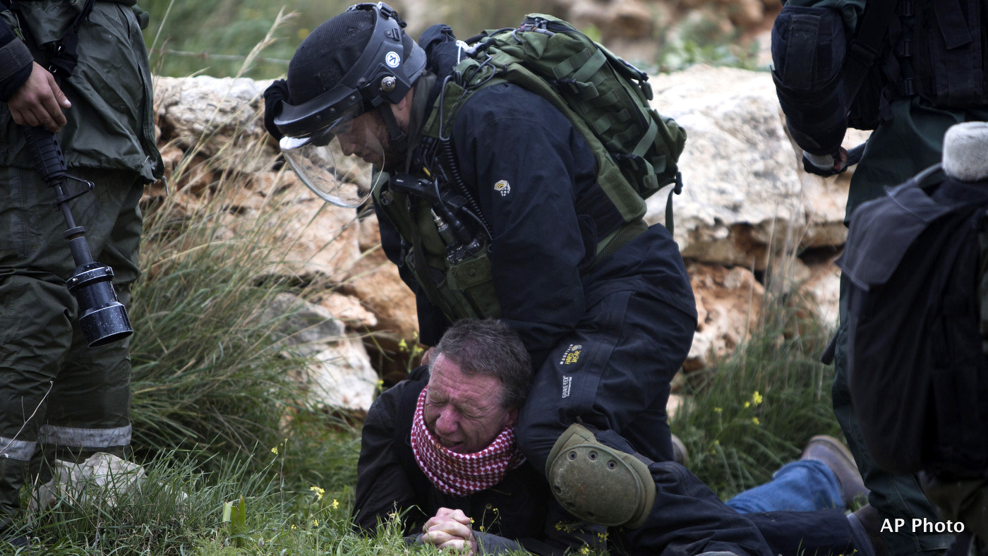 An Israeli border policeman detains a Palestinian protester during a weekly demonstration against Israel's separation barrier in the West Bank village of Bilin near Ramallah, Friday, Feb. 13, 2015.