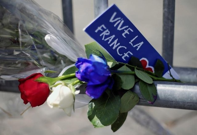 Flowers are seen attached to a fence to remember the victims of the Bastille Day truck attack in Nice in front of the French embassy in Rome, Italy, July 15, 2016. REUTERS/Max Rossi