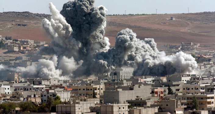 In this October 22, 2014, file photo, thick smoke from an airstrike by the US-led coalition rises in Kobani, Syria, as seen from a hilltop on the outskirts of Suruc, at the Turkey-Syria border.