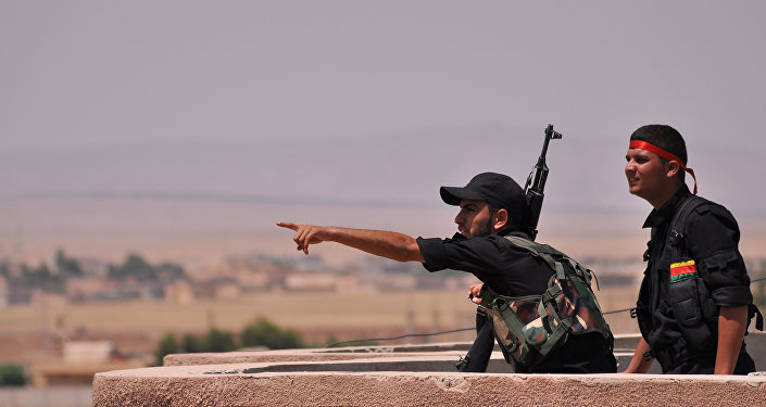 Fighters from the Kurdish People Protection Unit (YPG) monitor the horizon in the northeastern Syrian city of Hasakeh