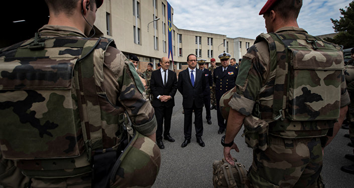 French President Francois Hollande (R) and Defence Minister Jean-Yves Le Drian review troops at the Army base and command centre for France's 'Vigipirate' plan, dubbed 'Operation Sentinelle', at the fort of Vincennes, on the outskirts of Paris, France, July 25, 2016