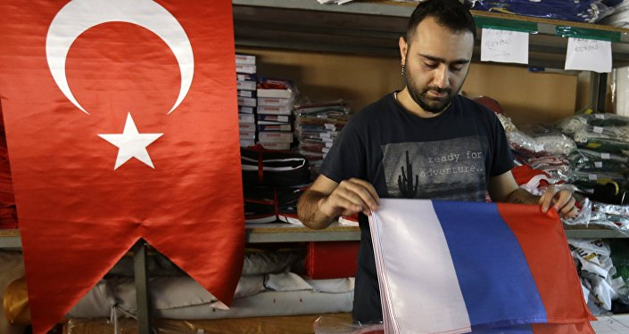 An employee of a flag-making factory folds a Russian flag as a Turkish flag adorns the display at left, in Istanbul, Tuesday, Aug. 9, 2016