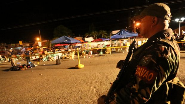 A Philippine soldier keeps watch at the bombing site in Davao, Philippines on Friday.