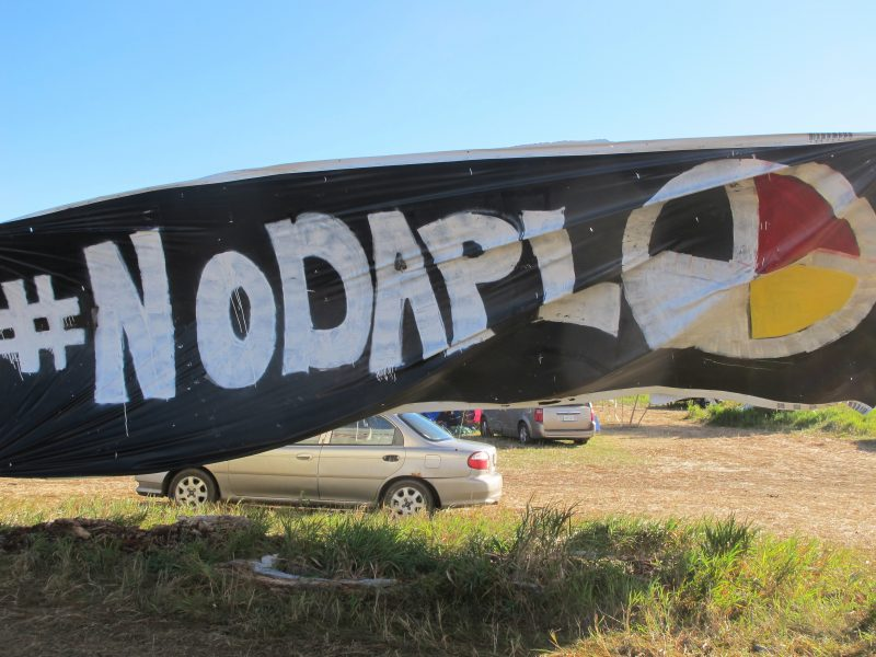 """A banner protesting the Dakota Access oil pipeline is displayed at an encampment near North Dakota's Standing Rock Sioux reservation on Friday, Sept. 9, 2016. The Standing Rock Sioux tribe's attempt to halt construction of an oil pipeline near its North Dakota reservation failed in federal court Friday, but three government agencies asked the pipeline company to """"voluntarily pause"""" work on a segment that tribal officials say holds sacred artifacts. (AP Photo/James MacPherson)"""