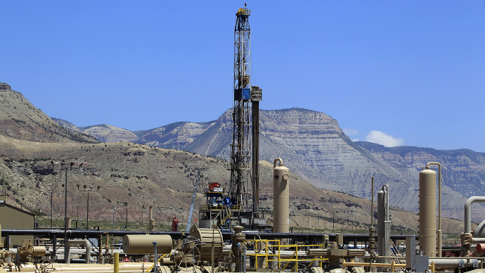 A natural gas drilling rig operates as natural gas piping rises from underground outside  Rifle, Colorado (Reuters / George Frey)