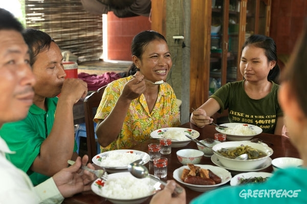 Ecological farmer Sovanry Nhem and her family enjoy an ecological meal at home in Cambodia. © Peter Caton / Greenpeace