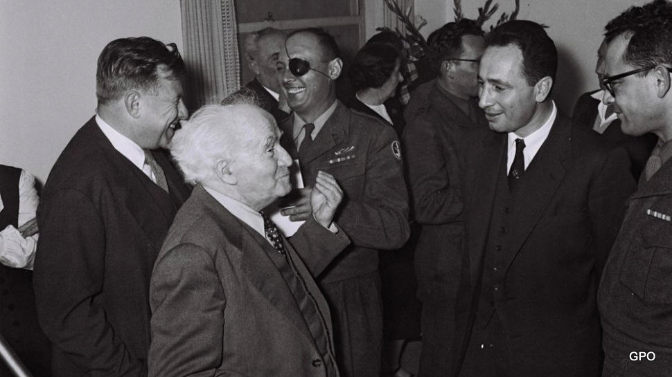 Prime Minister David Ben Gurion with his chief aide, Shimon Peres. In background: defense minister Moshe Dayan and Ben Gurion aide, Teddy Kollek.