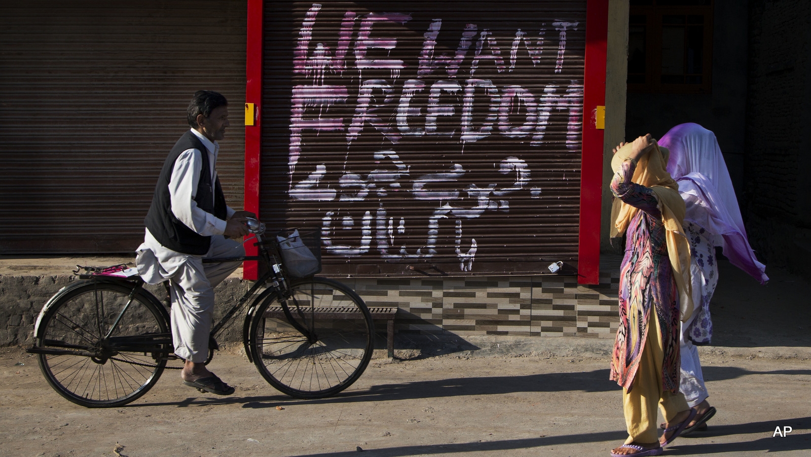 Kashmiri women walk past a closed market with graffiti painted on the shutter of a shop in Urdu that reads